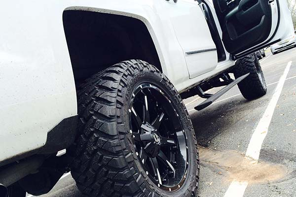 amp power steps shown on lifted white truck