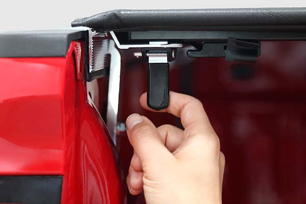 Single finger release to open and automatically latches when tonneau cover is closed